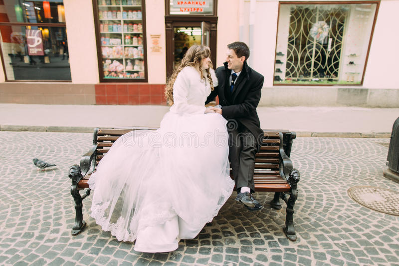 新娘和新郎浪漫夫妇坐在老镇街道的长木凳 免版税库存照片