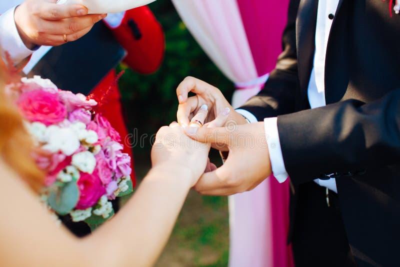 新娘和新郎的婚戒和手 在仪式的年轻婚礼夫妇 婚姻 爱的男人和妇女 两愉快的人c 免版税库存图片