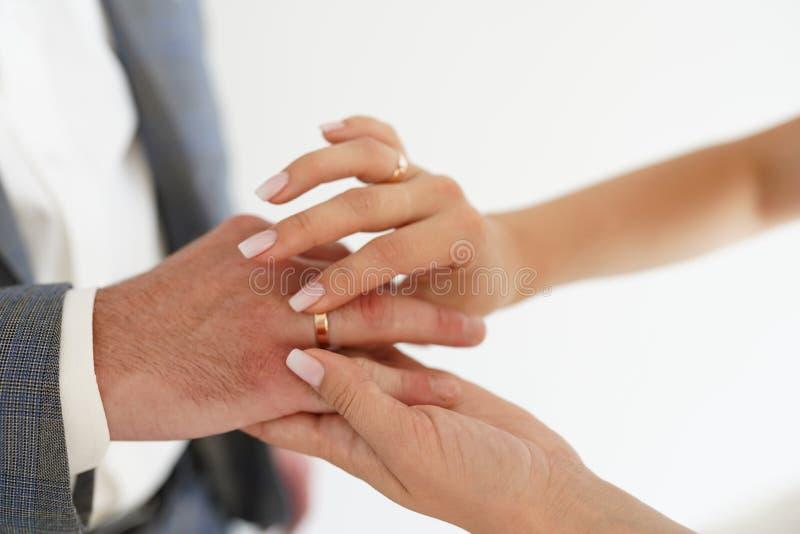 新娘和新郎的手与圆环在白色背景 爱和婚姻的概念 库存照片
