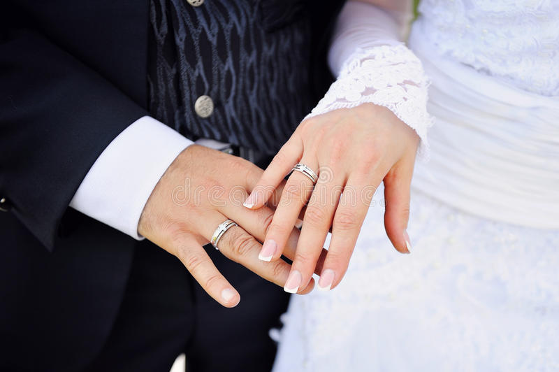 新娘和新郎的手与圆环 免版税库存照片