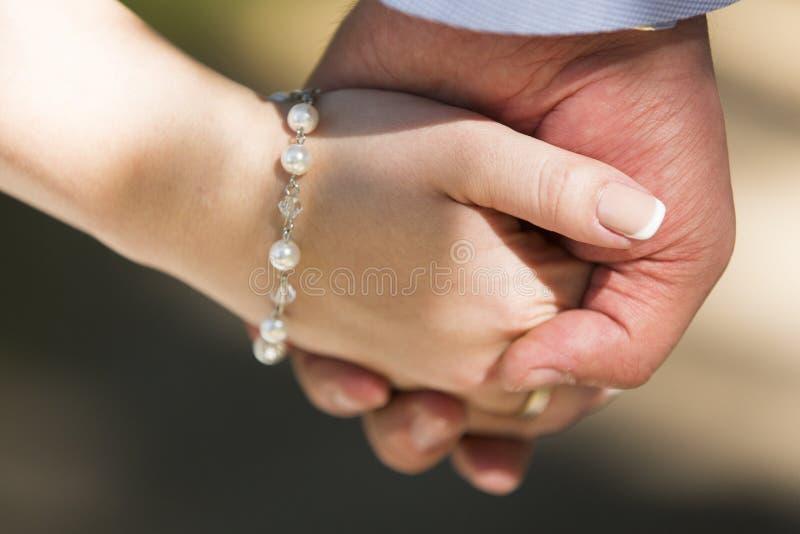 新娘和新郎的手与珍珠镯子 免版税图库摄影