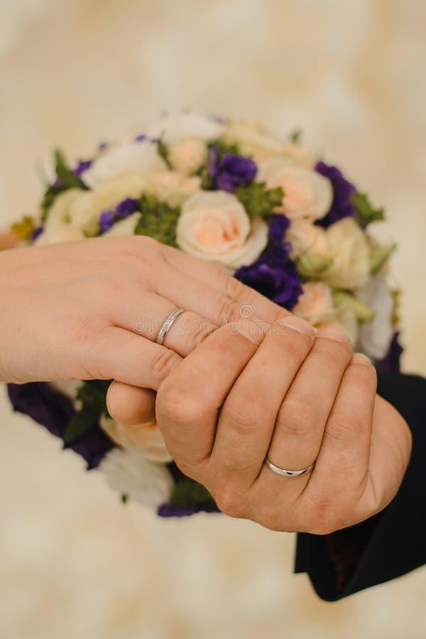 新娘和新郎的手与结婚戒指在精美花束的背景 库存图片