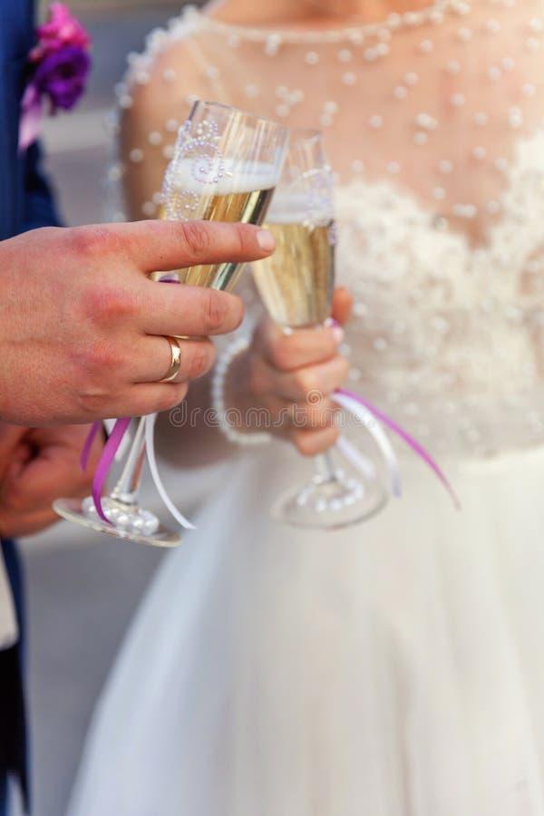 新娘和新郎的手使玻璃叮当响用香槟 免版税库存图片