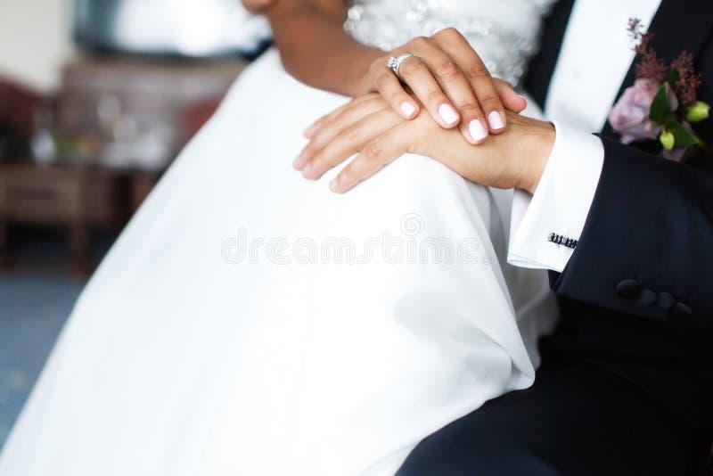 新娘和新郎的手在礼服 库存照片