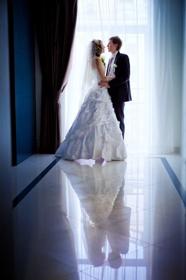 新娘和新郎的现出轮廓的画象在旅馆大厅里 免版税库存照片