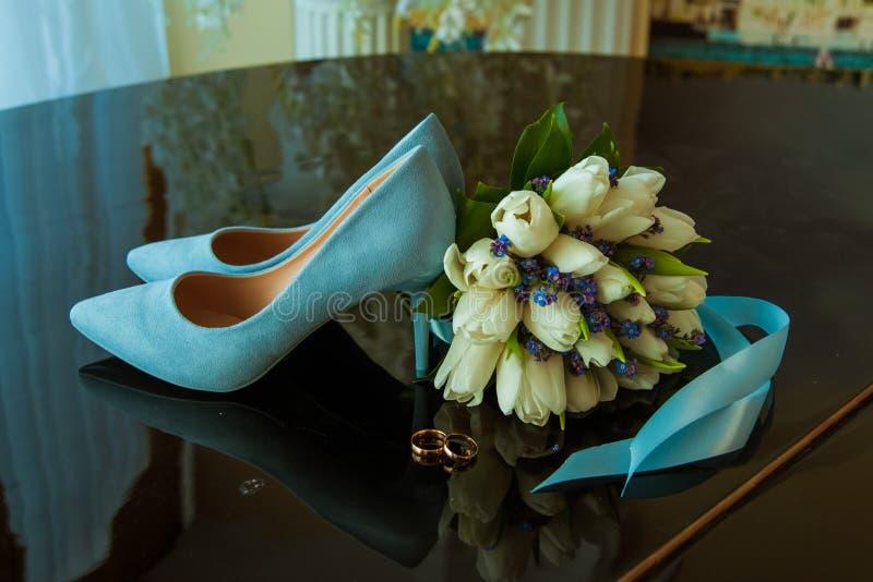 新娘和新郎的结婚戒指在白色郁金香美丽的婚姻的花束  蓝色婚姻的鞋子 免版税图库摄影