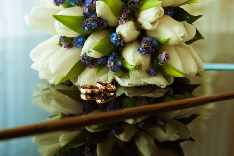 新娘和新郎的结婚戒指在白色郁金香美丽的婚姻的花束  库存照片