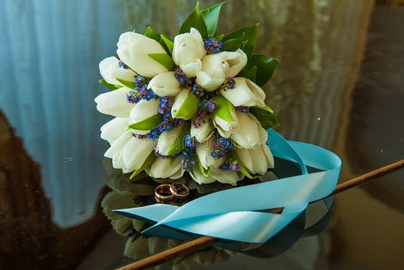 新娘和新郎的结婚戒指在白色郁金香美丽的婚姻的花束  免版税库存照片