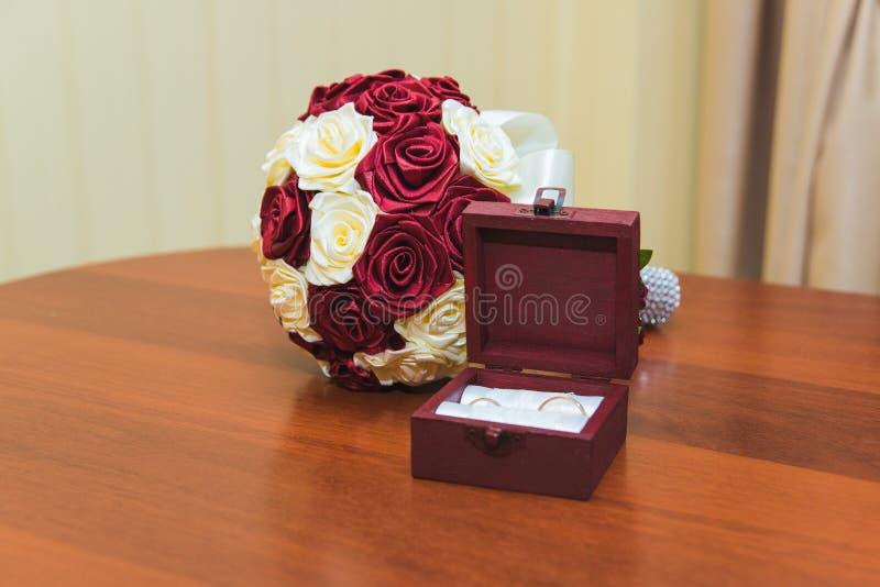 新娘和新郎的结婚戒指在红色和白玫瑰美丽的婚姻的花束  结婚戒指的木箱 免版税库存照片