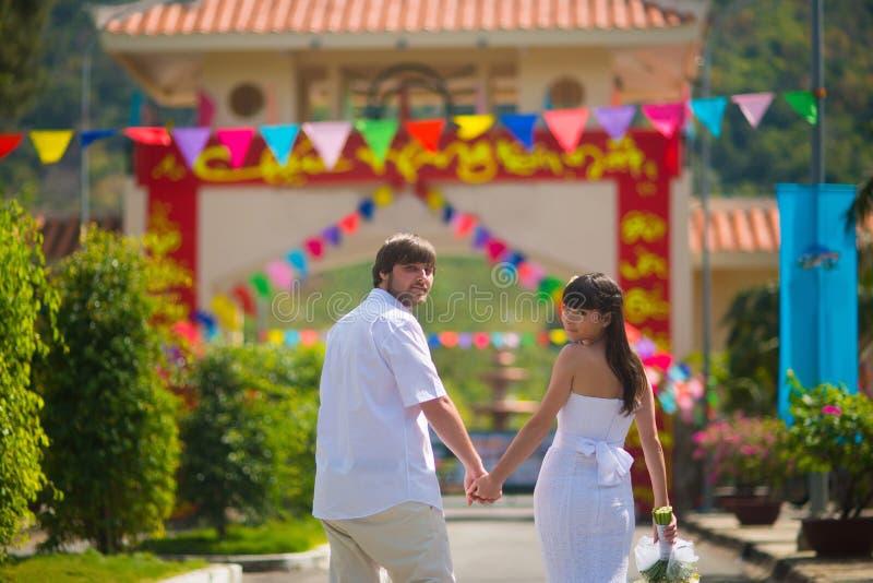 新娘和新郎看照相机,离开夏天公园户外,握手 免版税库存照片