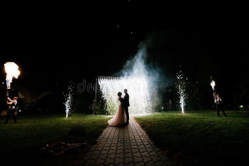 新娘和新郎立场在婚姻的曲拱晚上 免版税库存图片