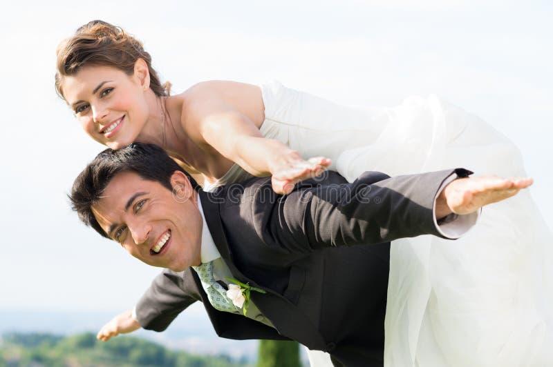 新娘和新郎肩扛 免版税库存照片