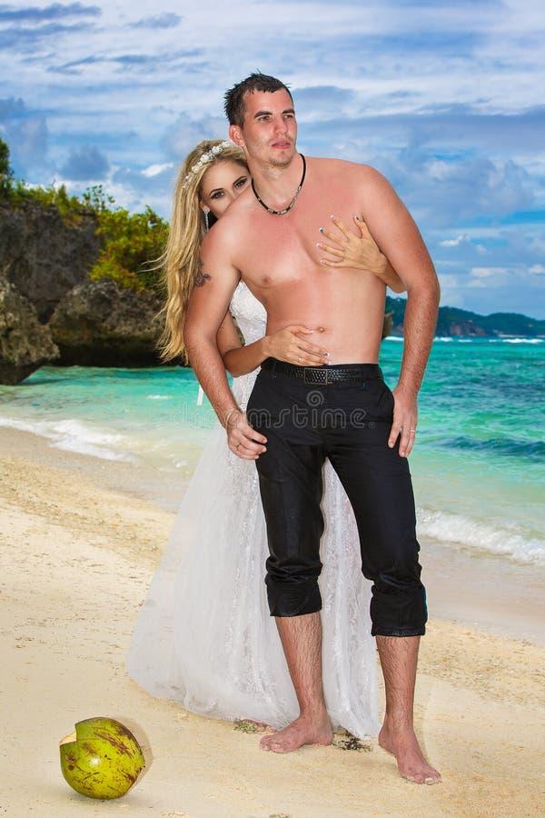 新娘和新郎获得在一个热带海滩的一个乐趣 库存照片