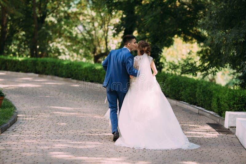 新娘和新郎被决定从他们的婚礼逃脱和急,以便没人看见他们 在奔跑人 免版税库存图片