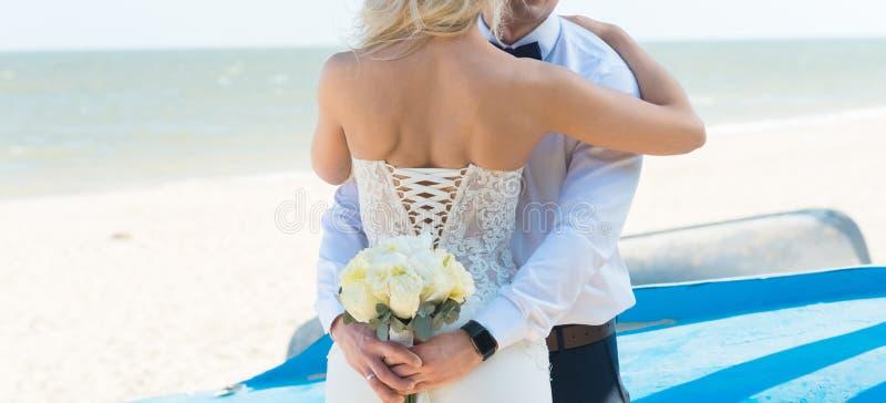 新娘和新郎,亲吻在一个美丽的海滩的日落,浪漫已婚夫妇 免版税库存照片