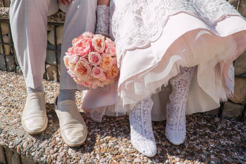 新娘和新郎,婚姻的鞋子的脚 从桃红色玫瑰的婚姻的花束 库存图片