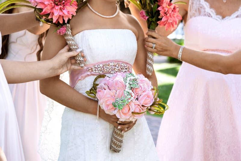 新娘和bridemaids在一婚礼那天在手上拿着花束 库存照片