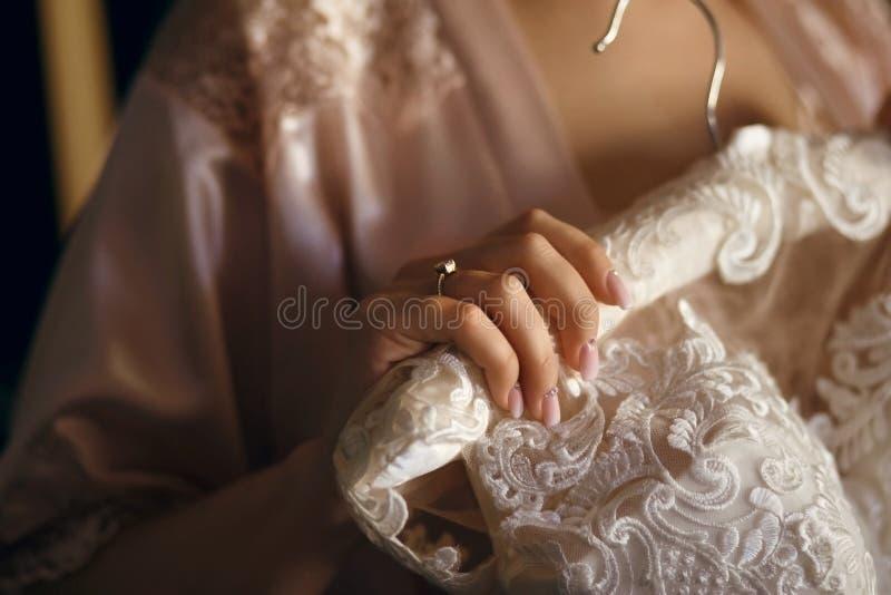 新娘在她的手上在挂衣架拿着一件白色礼服,在她的手指是结婚戒指,礼服垂悬 图库摄影