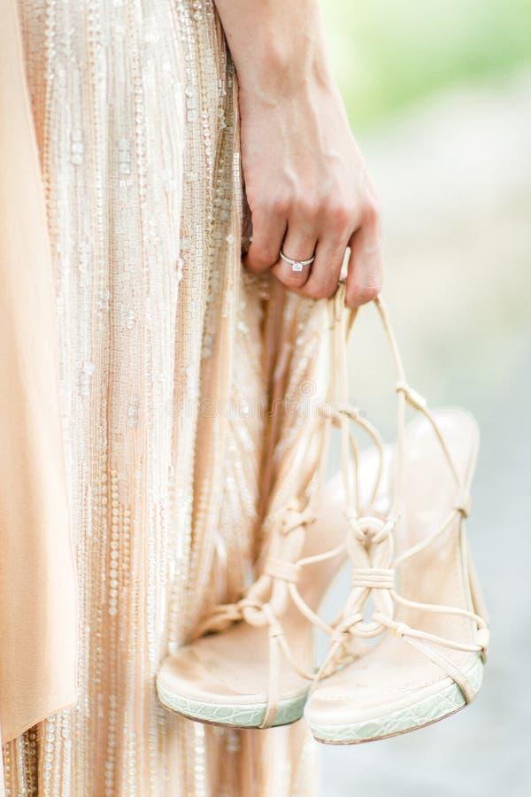 新娘在她的手上拿着鞋子,婚姻的鞋子和婚戒 轻的鞋子在女孩的手上 库存照片