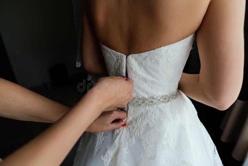 新娘在婚礼礼服的` s后面 女傧相` s手拿着束腰  库存照片
