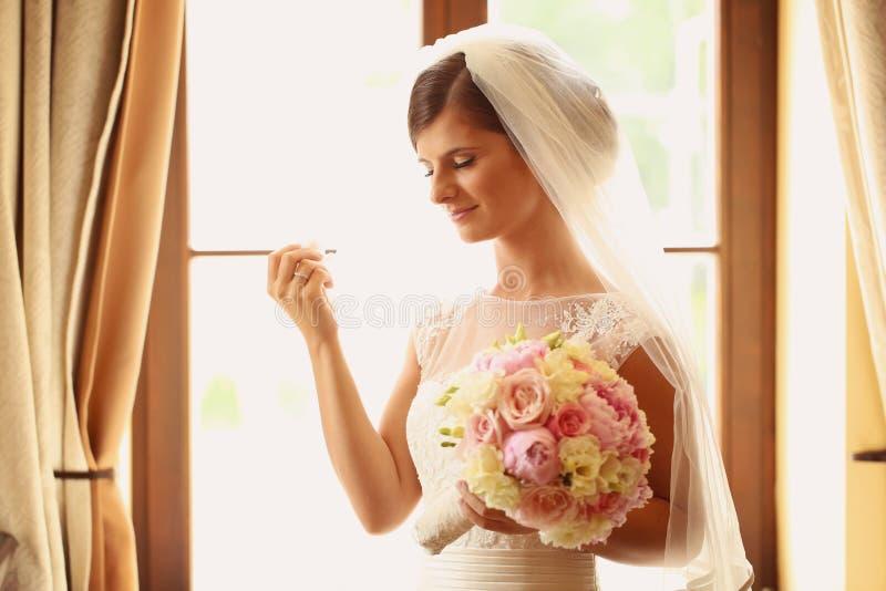 新娘在拿着她的婚礼花束的旅馆客房 库存照片