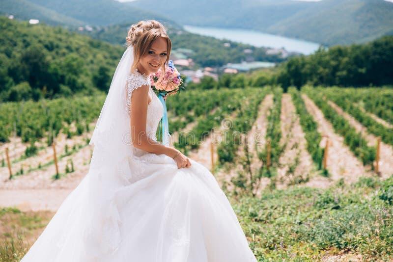 新娘在晴天笑并且高兴 女孩在她的手和步行上拿着花别致的花束在中 图库摄影