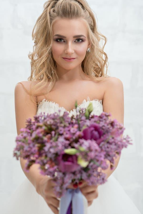 年轻新娘在有精妙的花束的演播室 免版税库存照片