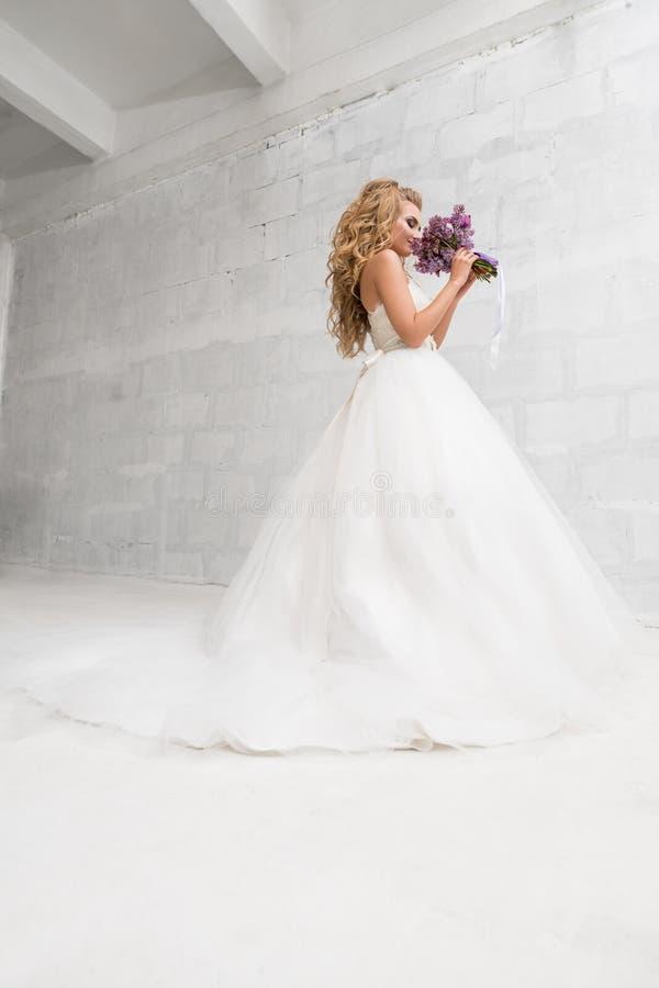 年轻新娘在有精妙的花束的演播室 免版税库存图片