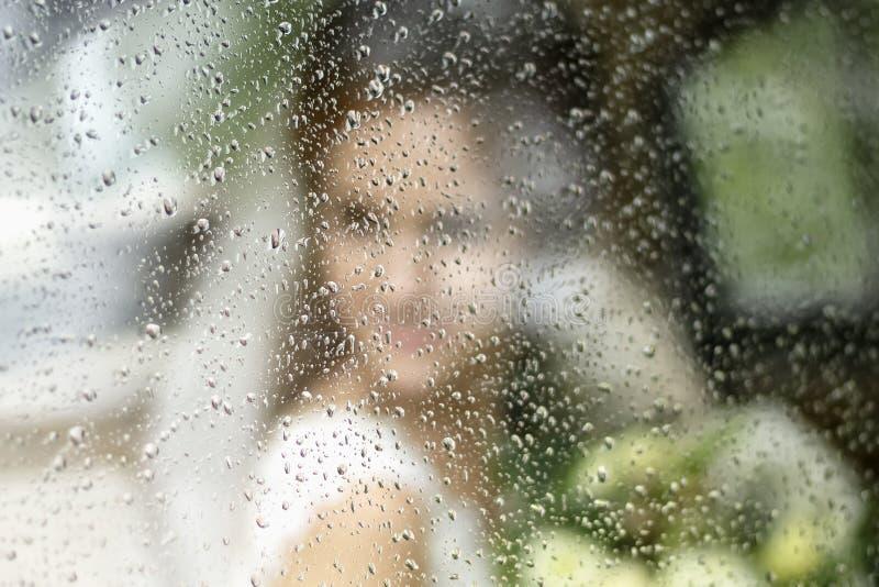 新娘在有花束的一婚纱现出轮廓通过在雨下落的玻璃 免版税库存图片