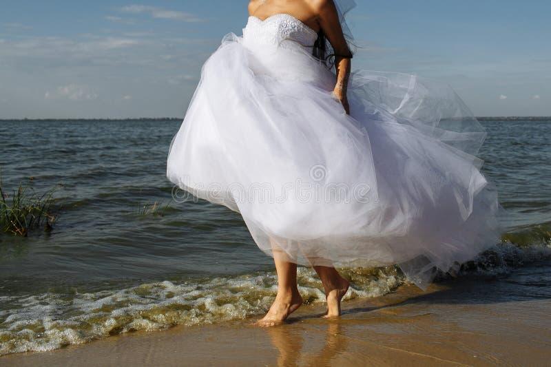 新娘在海浪线跑 免版税库存图片
