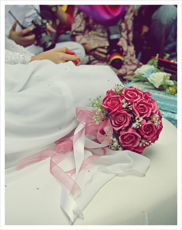 新娘在红色玫瑰等待的隆重的庆后花束坐 免版税库存图片