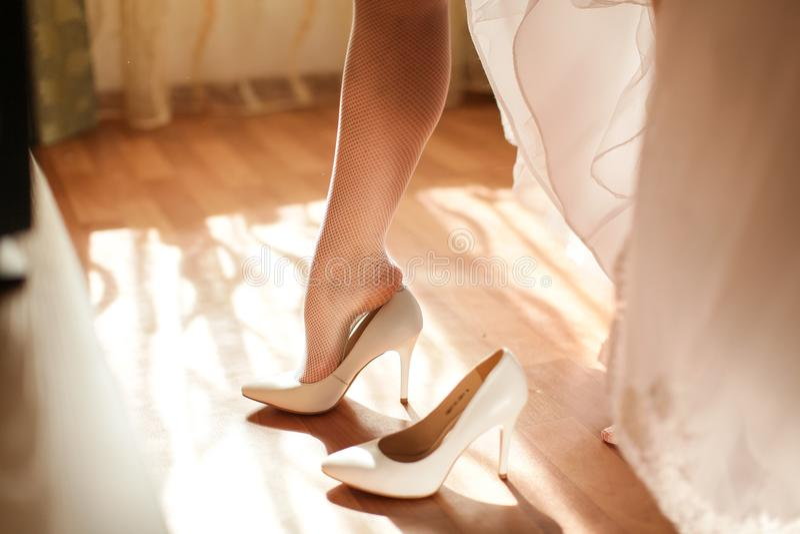 新娘在脚上把白色鞋子放早晨在仪式,选择聚焦前 免版税库存图片