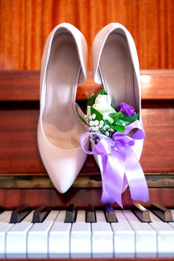 新娘在钢琴,新娘` s花束的` s鞋子 婚姻的属性 免版税图库摄影