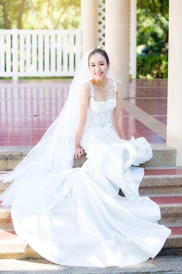 新娘坐与花 摆在公园的美丽的少妇 免版税库存照片