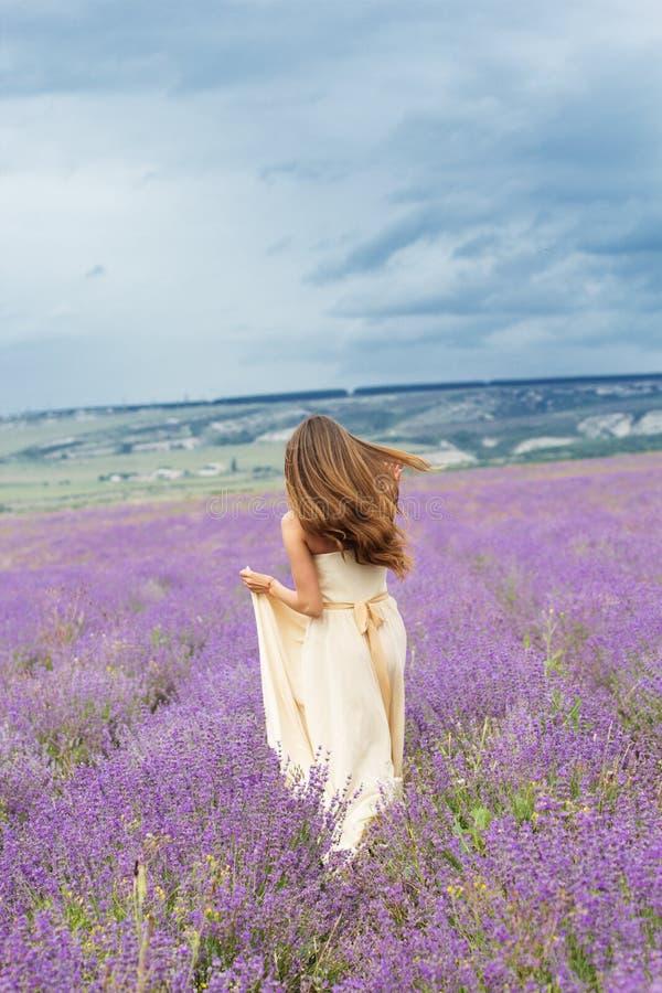 新娘女孩跑在淡紫色领域 免版税库存图片