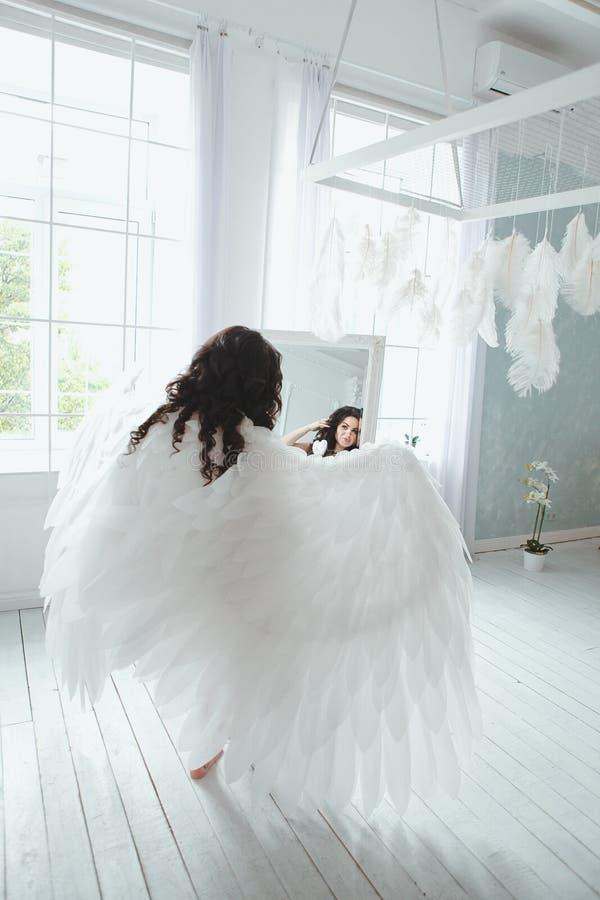 新娘女用贴身内衣裤和天使的肉欲和美丽的女孩飞过看在镜子 免版税库存图片