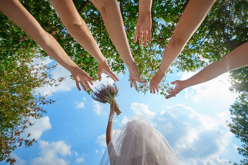 新娘投掷花束给婚姻传统的未婚的女孩 库存照片
