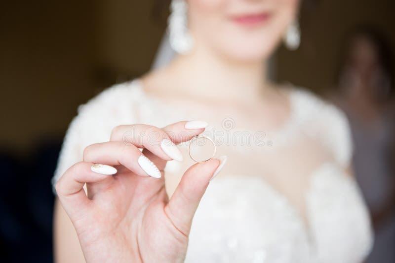 新娘拿着一个婚戒 特写镜头 库存照片