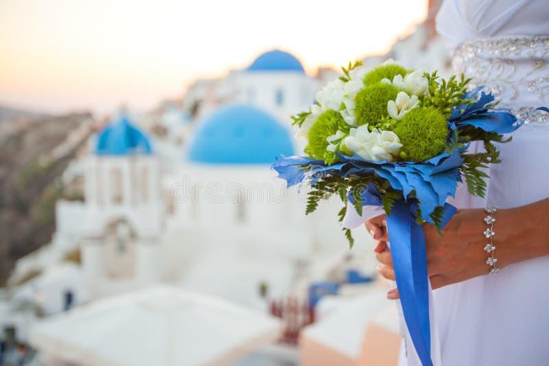 新娘拿着在白色和绿色的婚姻的花束和蓝色装饰反对日落的背景在圣托里尼,希腊的 库存图片