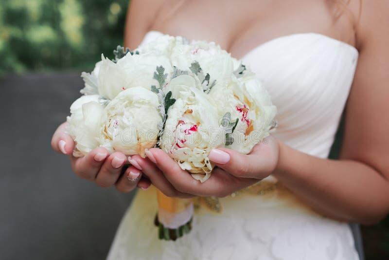 新娘拿着婚礼花束 免版税库存图片