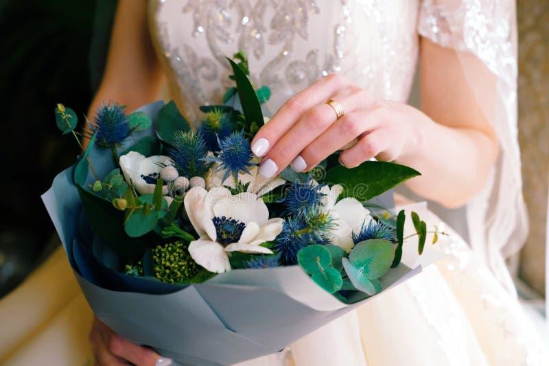 新娘拿着惊人的婚礼花束 免版税库存照片