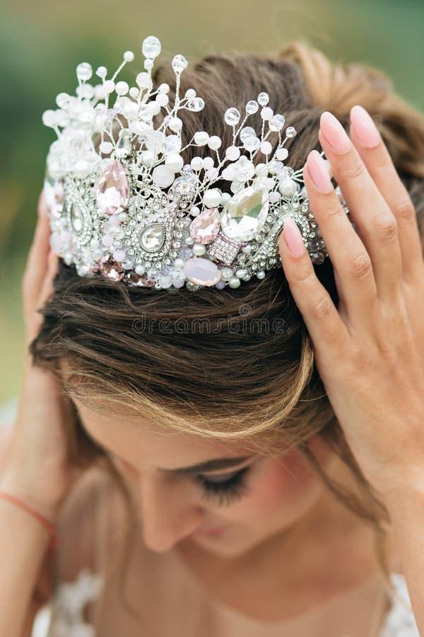 新娘拿着桃红色冠用两只手 免版税图库摄影