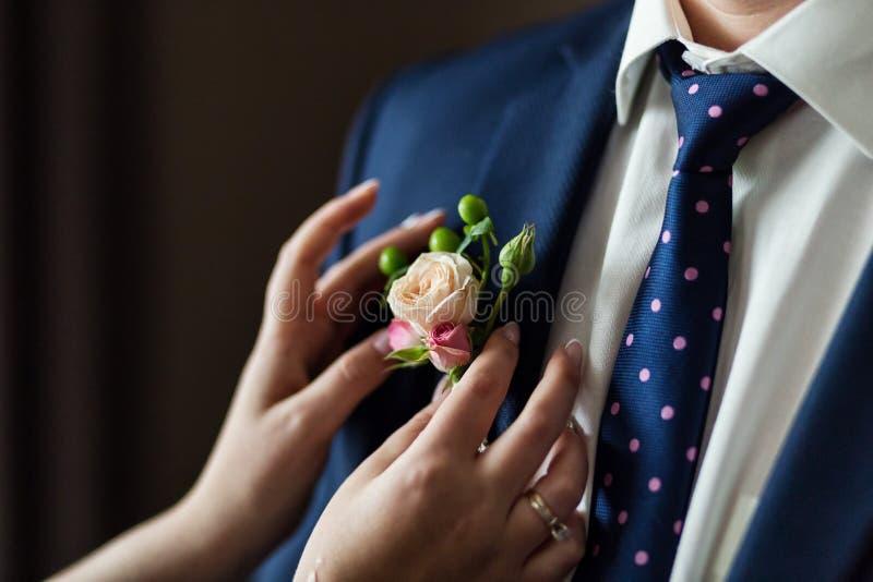 新娘改正在夹克的新郎钮扣眼上插的花在他们的婚礼clos 免版税库存图片