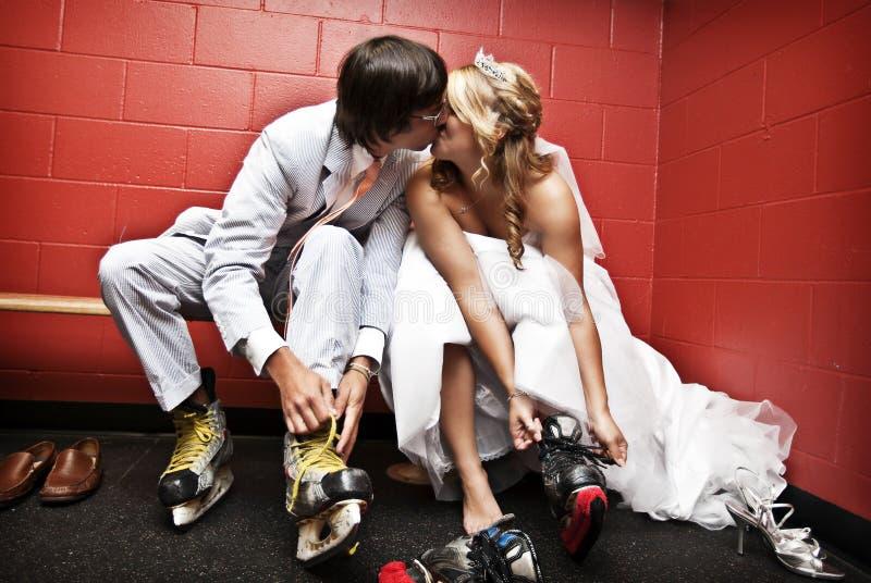 新娘放置冰鞋的新郎冰 免版税库存图片