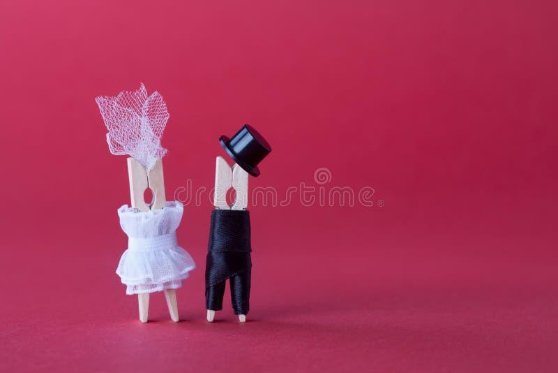 新娘新郎婚礼邀请卡片模板 在爱的晒衣夹字符 桃红色紫罗兰色纸背景拷贝空间 免版税库存照片