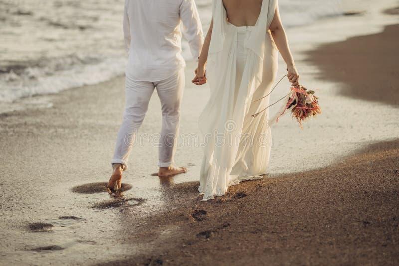新娘新郎走在浪潮起伏的海滩的,新娘有花在她的手 库存图片