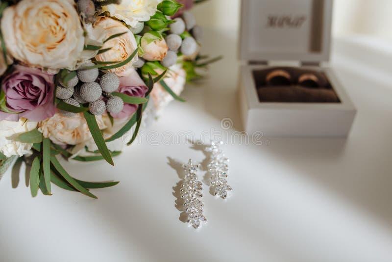 新娘早晨详述构成 婚戒顶视图,花美丽的花束与丝带,耳环的 平面 免版税图库摄影
