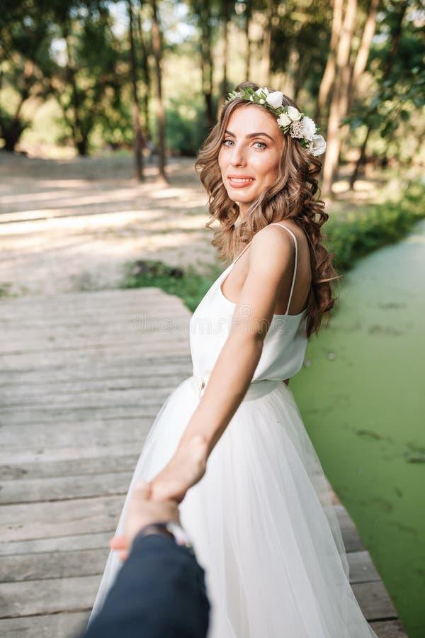 新娘是新郎的手在公园在湖附近 跟随m 库存照片