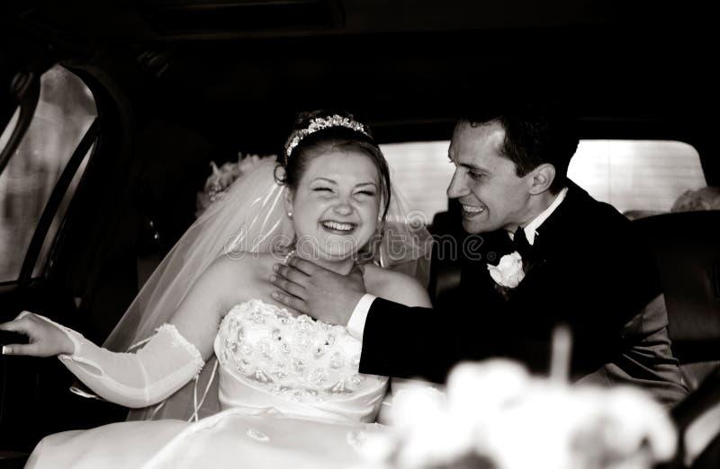 新娘有乐趣的新郎大型高级轿车 免版税图库摄影