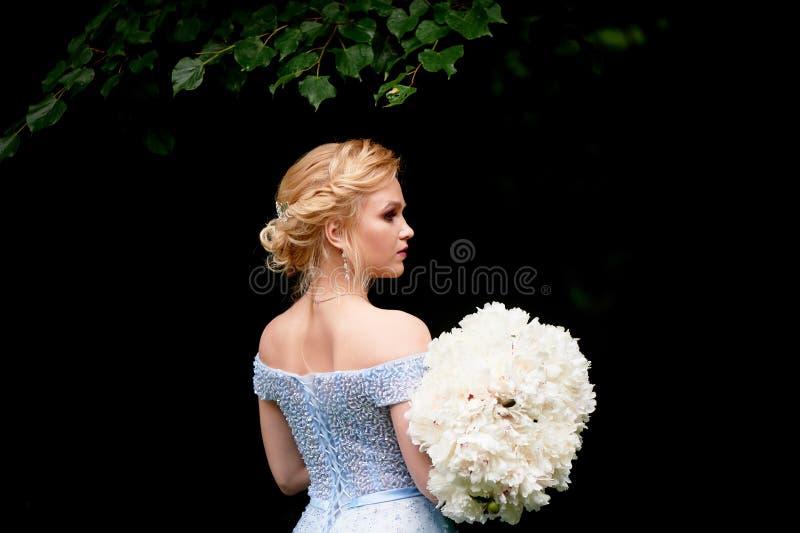 新娘本质上,与牡丹大花束  在蓝色,被绣的礼服 婚姻的步行,照片写真 免版税图库摄影